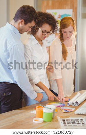 Business people with color samples standing by desk in ofice