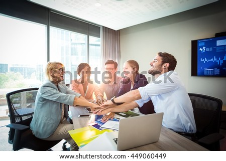 Business people with hand stacked during meeting in the office - stock photo