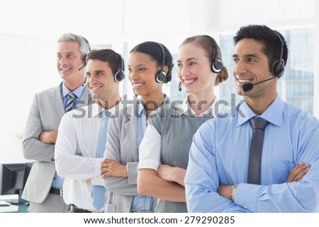 Business people with headsets looking at right in office