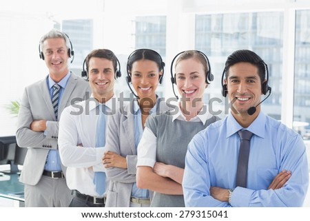 Business people with headsets smiling at camera in office