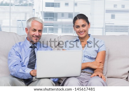 Business people with laptop smiling at camera on couch in staffroom - stock photo