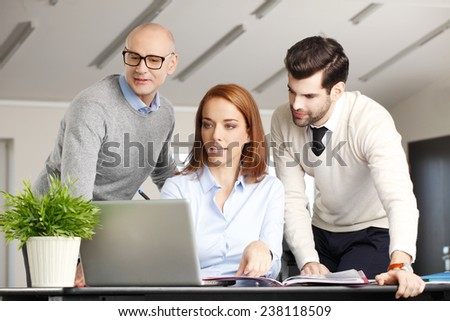 Business people with laptop working on project while sitting at office. Teamwork. - stock photo
