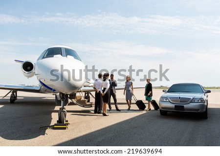 Business people with pilot and airhostess standing near private jet and limo at terminal