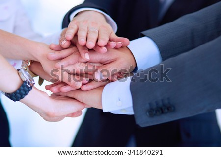 Business people with their hands together in a circle - stock photo