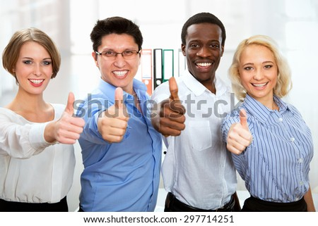 Business people with thumbs up and smilingin in office - stock photo