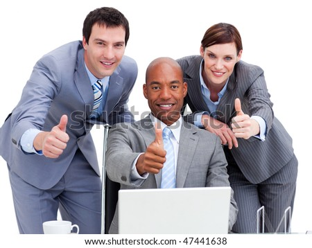Business people with thumbs up looking at a laptop against a white background - stock photo