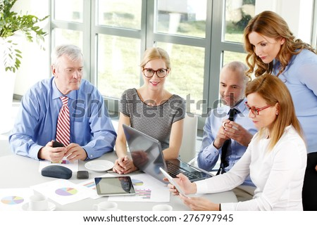 Business people working at office. Busy businesswoman holding digital tablet in her hands while business colleagues sitting at conference desk in front of laptop and working on financial plan.  - stock photo