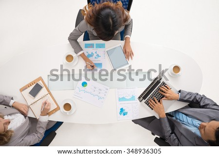 Business people working at the same table, view from above