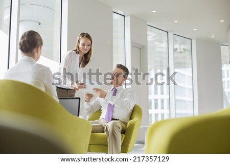 Business people working in office lobby - stock photo
