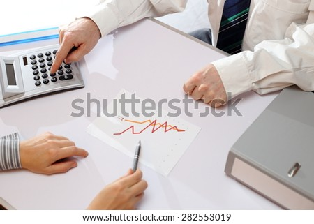 business people working in office with calculator - stock photo
