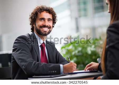 Business people working on a document while sitting in a coffee shop  - stock photo