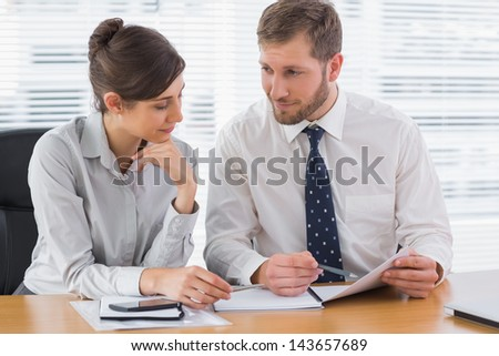 Business people working on documents together at desk in office - stock photo