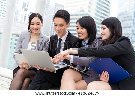 Business people working on laptop computer together