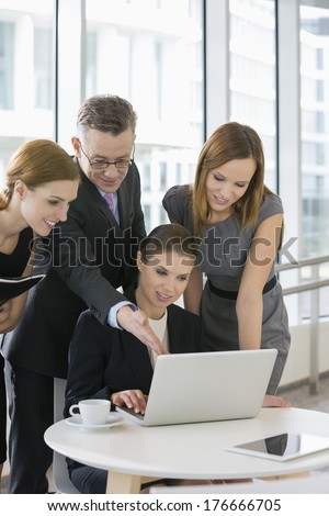 Business people working on laptop in office cafeteria - stock photo