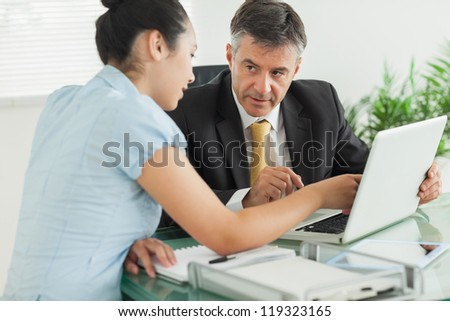 Business people working on laptop together in an office - stock photo