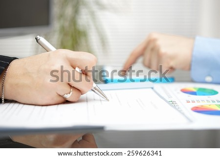 business people working on meeting and analyzing numbers on document and tablet - stock photo