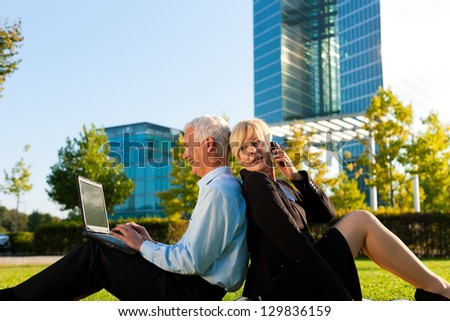 Business people working outdoors - he is working with laptop, she is calling someone on phone - stock photo