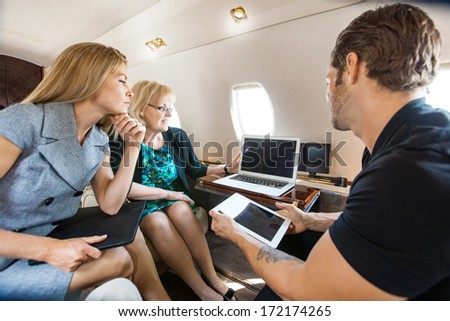 Business people working together on laptop and digital tablet in private jet - stock photo