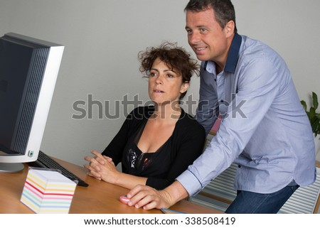 Business people working together on laptop in office at desk - stock photo
