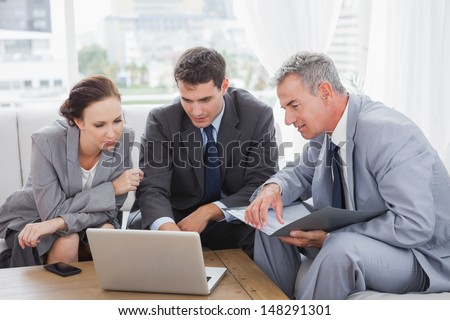 Business people working together on their laptop in cosy meeting room - stock photo