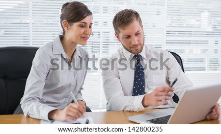 Business people working together with laptop at desk in office - stock photo
