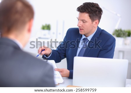 Business people working with laptop in an office, sitting ta the desk - stock photo