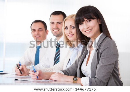 Business People Writing Meeting Notes In Office - stock photo