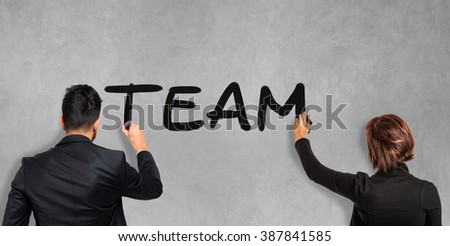 Business people writing the word Team on the screen - stock photo