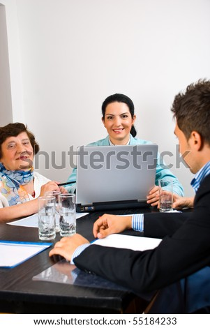 Business people young and elderly having a meeting in office and using laptop - stock photo