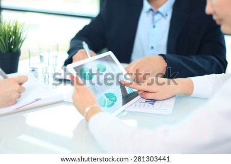 Business person analyzing financial statistics displayed on the tablet screen  - stock photo