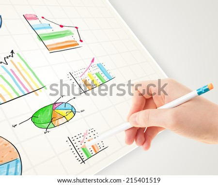 Business person drawing colorful graphs and icons on plain paper - stock photo