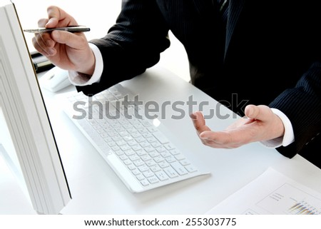 Business person explaining while looking at pc display - stock photo