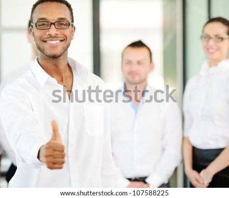 Business person giving you thumb up with colleagues in background - stock photo