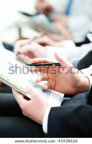 Business person hand with pen learning document during lecture - stock photo