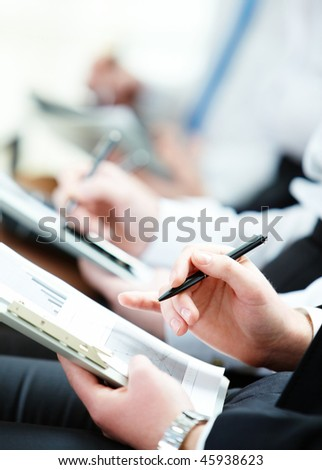 Business person hand with pen pointing at document during lecture - stock photo