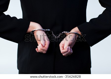 Business person handcuffed behind back - stock photo