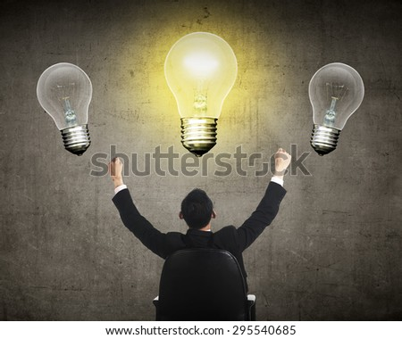 Business person having bright idea light bulb concept over grunge background - stock photo