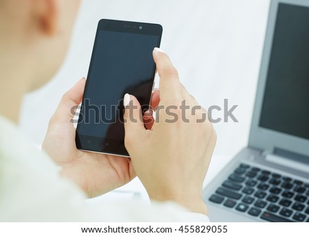 Business person holding modern smart phone and touching on a blank screen.. - stock photo