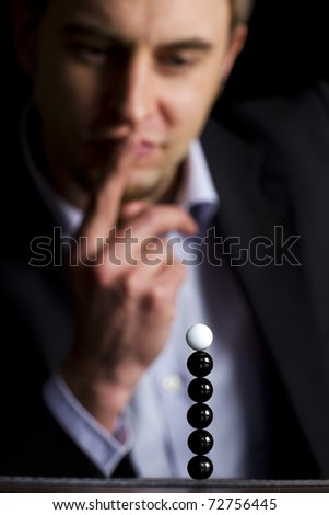 "Business person in dark suit sitting at office desk and looking at stack of balls thinking about new business ventures, symbolizing ""everything is possible"", low-key image. - stock photo"