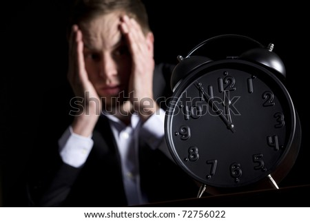 Business person in dark suit sitting at office desk with hands at head being worried with close up of clock in foreground showing five minutes to twelve, low-key style isolated on black background.
