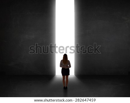 Business person looking at wall with light tunnel opening concept - stock photo