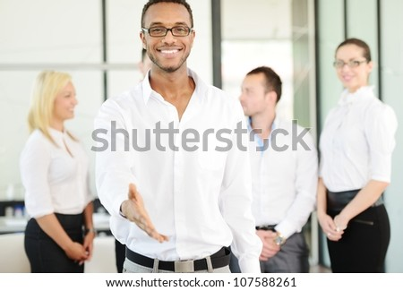Business person offering you handshake with colleagues in background - stock photo