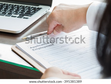 Business person's women hand filing blank application for employment form paper on office table desk: Fill in empty document template applying for professional job career for business human resources