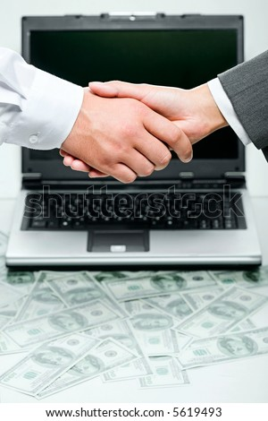 Business person shaking hands over opened laptop and heaps of money on the background - stock photo