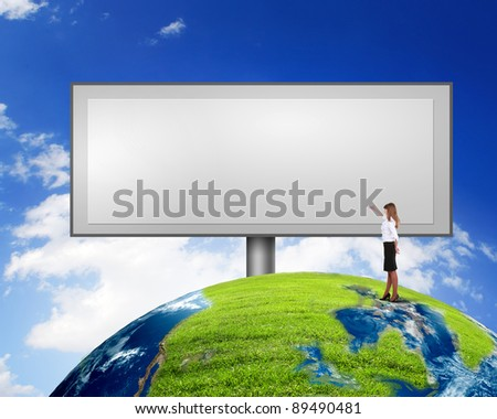 Business person standing near a blank  billboard - stock photo