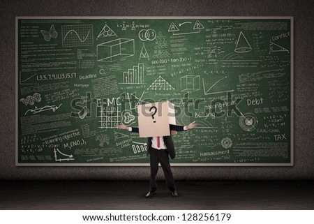 Business person with question mark in front of blackboard