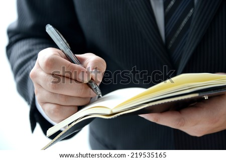 Business person writing on personal organizer - stock photo