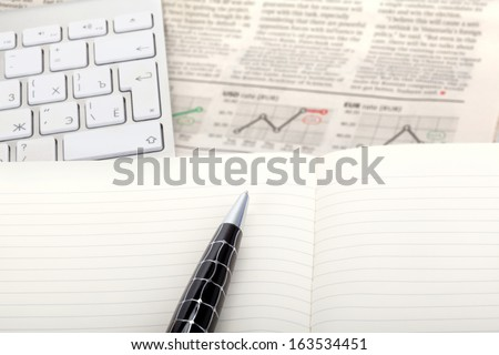 Business photo: fresh newspaper with stock index overview and open note with keyboard - stock photo