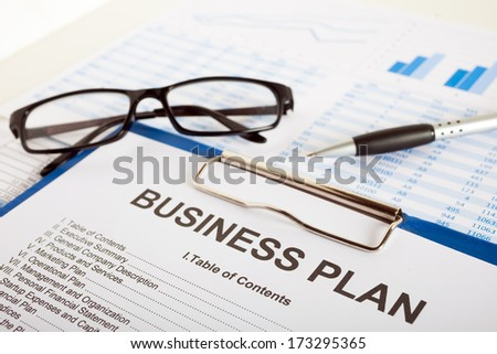 Business plan over financial charts - stock photo