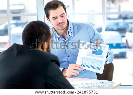 Business plan. Two confident businessman sitting at the negotiating table in the office and on the paper considered business plan. Business people dressed in formal wear - stock photo